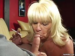 Busty blondie gives head while smoking